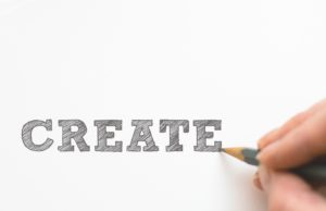 hand writing the word create in large blocks with pencil